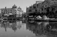 I Calafatari tra la Darsena e il Porto Piccolo. Riflessi e imbarcazioni. Nello sfondo il Palazzo delle Poste.  - Siracusa (2024 clic)