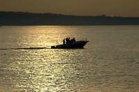 Barca fotografata sullo sfondo di Milazzo al tramonto del sole  - Venetico (4984 clic)