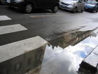 la pozzanghera dopo un temporale,  riflessi sull'a pozzanghera l'immagine dei palazzi ed il cielo nu