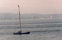Tipica barca per la pesca al pescespada e sul fondo la costa calabrese ed alcuni traghetti negli invasi.  - Messina (16395 clic)