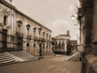 La via Crociferi prende il nome dalla chiesa di S. Camillo dei Padri Crociferi che si trova proprio alla fine della strada. E' una via di straordinaria forza suggestiva, ricca di chiese, chiusa dal portale d'ingresso di villa Cerami (oggi facoltà di Giurisprudenza). Fu ricavata a metà altezza del pendio collinare sul quale poggiano anche il Teatro e l'Odeon romani e aveva lo scopo di collegare la Porta del Re (sopra piazza Stesicoro) con il piano di S. Filippo (la piazza Mazzini).  - Catania (18527 clic)