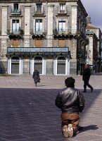 Piazza Università.Un mendicante di spalle, in ginocchio, che chiede l'elemosina.  - Catania (5507 clic)