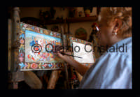 la Pittrice Venera Sapienza al lavoro  su una sponda di carretto  - Aci sant'antonio (5699 clic)