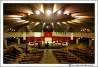 Siracusa. La costruzione a pianta circolare (vanta ben 18 ingressi), dal diametro esterno di 80 metri, accoglie la chiesa inferiore o Cripta , inaugurata nell'agosto del 1968, e la chiesa superiore o Santuario, la cui base è sostenuta da 22 travi di cemento armato con un diametro interno di 71.40 metri. All'interno della Cripta, al centro, è situato l'altare maggiore, su cui impera il quadretto della Madonnina.     - Siracusa (4011 clic)