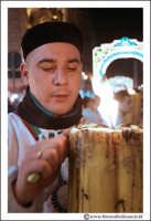 Catania: Festa di Sant'Agata. 5 Febbraio 2005: Festa della Patrona di Catania, Sant'Agata. Via Etnea. Ragazzo devoto, pulisce un cerone #1.  - Catania (2066 clic)