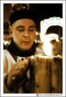 Catania: Festa di Sant'Agata. 5 Febbraio 2005: Festa della Patrona di Catania, Sant'Agata. Via Etnea. Ragazzo devoto, pulisce un cerone #2 (foto antichizzata con photoshop).  - Catania (2188 clic)