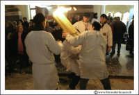 Catania: Festa di Sant'Agata. 5 Febbraio 2005: Via Etnea. Alcuni ragazzi devoti a Sant'Agata, aiutano a caricare il pesante cerone acceso, sulle spalle di un loro amico.  - Catania (2370 clic)