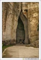 ORECCHIO DI DIONIGI o DIONISIO. E' una grotta artificiale, imbutiforme, scavata nel calcare, alta circa 23 m. e larga dai 5 agli 11 m., con una singolare forma, vagamente simile ad un padiglione auricolare, che si sviluppa in profondità per 65 m., con un insolito andamento ad S e con sinuose pareti che convergono in alto, in un singolare sesto acuto. La grotta è, inoltre, dotata di eccezionali proprietà acustiche (i suoni vengono amplificati fino a 16 volte).   - Siracusa (4238 clic)
