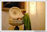Mazzarino (CL). Chiesa Madre. Interno, La fonte battesimale e il sacerdote. MAZZARINO Walter Lo Casc