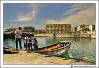 Siracusa - Ortigia - Lungomare: Marinaio aiuta dei turisti a scendere dalla sua imbarcazione, dopo aver fatto un giro turistico.  - Siracusa (2656 clic)