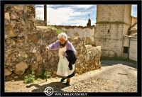 Agira. Quartiere Santa Maria. Una povera vecchietta, sale una stradina aiutandosi con il suo bastone.  - Agira (3975 clic)