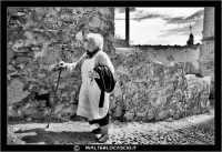 Agira. Quartiere Santa Maria. Una povera vecchietta, sale una stradina aiutandosi con il suo bastone. #2   - Agira (1502 clic)