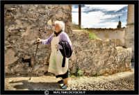 Agira. Quartiere Santa Maria. Una povera vecchietta, sale una stradina aiutandosi con il suo bastone. #3  - Agira (3541 clic)