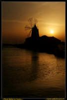 Marsala: Le Saline al Tramonto. La strada che da Trapani conduce a Marsala, costeggiando la laguna che accoglie Mozia, ý fiancheggiata da saline che offrono una vista bellissima: gli specchi d'acqua suddivisi da sottili strisce di terra formano una scacchiera irregolare e multicolore. Foto Walter Lo Cascio www.walterlocascio.it  - Marsala (2745 clic)