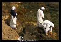 Acicastello. Suore che si lavano i piedi a mare sotto il castello.  - Aci castello (1495 clic)