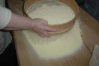 Processo di panificazione nelle zone rurali del Val di Noto. La farina viene setacciata con lo scaniaturi nella maidda  - Granieri (6125 clic)