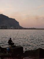 pescatore nel suo far d'esca accarezza con lo sguardo l'aspezza di monte Pellegrino al tramonto. (Fo