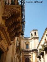 Splendido balcone figurato del barocco Palazzo Nicolaci di Villadorata, sullo sfondo la Chiesa di Montevergini  - Noto (4385 clic)