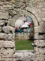 Il mercato di Ortigia attraverso la finestra del Tempio di Apollo. Realmente quest'apertura era una porta creata quando il Tempio venne trasformato in basilica Normanna. Le trasformazioni del Tempio sono numerose, nell'ordine Tempio Greco, Chiesa Bizantina, Moschea Araba, Basilica Normanna, Caserma Spagnola, Chiesa della Madonna delle Grazie in più vi vennero costruite pure delle case per civile abitazione  - Siracusa (1909 clic)