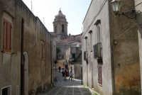 in fondo alla via acciottolata, il campanile della Chiesa Parrocchiale di San Giuliano - sec. XII - XVII  - 1 maggio 2008  - Erice (876 clic)