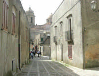 in fondo alla via acciottolata, il campanile e la cupola della Chiesa Parrocchiale di San Giuliano - sec. XII - XVII - 1 maggio 2008   - Erice (826 clic)
