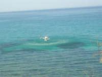 Il Monte Inici brucia! L'elicottero, impegnato nell'opera di spegnimento dell'incendio, sta facendo rifornimento d'acqua dal mare - 23 giugno 2006     - Castellammare del golfo (768 clic)