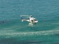 Il Monte Inici brucia! L'elicottero, impegnato nell'opera di spegnimento dell'incendio, sta facendo rifornimento d'acqua dal mare - 23 giugno 2006     - Castellammare del golfo (952 clic)