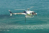 Il Monte Inici brucia! L'elicottero, impegnato nell'opera di spegnimento dell'incendio, sta facendo rifornimento d'acqua dal mare - 23 giugno 2006     - Castellammare del golfo (1052 clic)