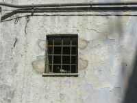Via Ten. Caravaglios - dietro la grata della finestrella di una vecchia casa due piccioni stanno preparando il loro nido - 17 luglio 2007  - Alcamo (728 clic)