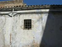 Via Ten. Caravaglios - dietro la grata della finestrella di una vecchia casa due piccioni stanno preparando il loro nido - 17 luglio 2007  - Alcamo (710 clic)
