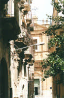 Via XI Febbraio, con ingresso e balcone di palazzo barocco, e Basilica di S. Maria Assunta - 19 agosto 2001  - Alcamo (1714 clic)