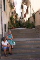 La bellissima isola Lipari. La signora vestita di azzurro indica alla sua amica che ha raccolto nel suo orto zucchine tante così!  - Lipari (4153 clic)