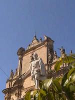 Statua di Pietro di Lorenzo Busacca con sullo sfondo la chiesa del Carmine.  - Scicli (1957 clic)