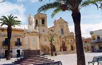 P.zza Umberto I, meglio conosciuta come p.zza S. Rocco. In primo piano la statua, sullo sfondo la chiesa di S. Rocco Patrono di Scordia  - Scordia (7623 clic)