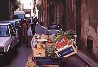 Venditore ambulante di frutta e verdura in Via Serisso con allo sfondo Porta Ossuna  - Trapani (7792 clic)